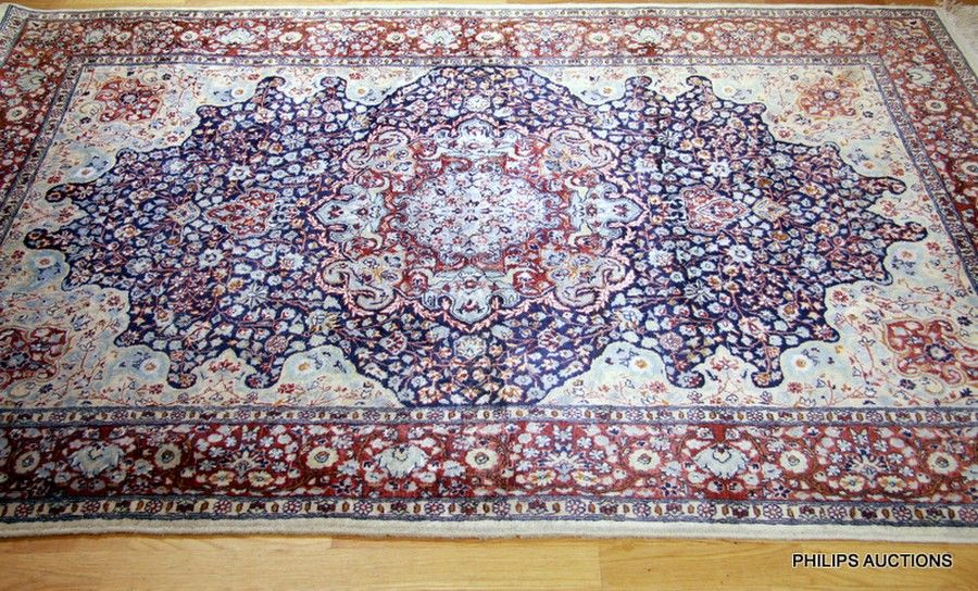 A Pakistani Wool Rug With A Rosette In Tan And Teal Colours