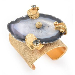 34d47021fc0 A cuff by Yves Saint Laurent, styled in gold metal with blue lace agate and  gem detail.