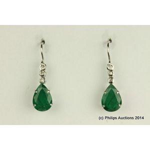 7766010db A pair of emerald and diamond earrings, 18ct white gold, made as fine  medium length drop earrings, each featuring a pear cut emerald of deep  green colour, ...