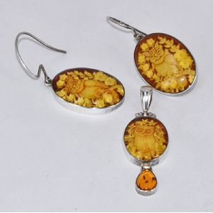 89929c5d7ad066 An amber set, comprising a pair of earrings and a pendant, all depicting  carved owl and set in sterling silver. Total weight 10.9g. Show 2 more like  this