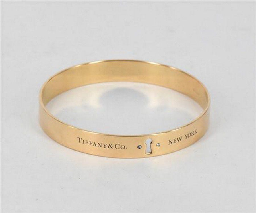 6d5f20517 A Tiffany & Co 'Locks' bangle, 18 carat yellow gold, set with ...