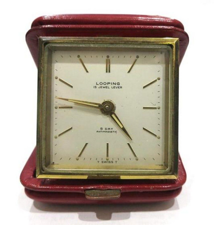 A Looping, Swiss travel clock in a red leather case, cream ...